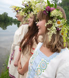 Three girls. In camomile chaplet and traditional clothes royalty free stock image