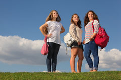 Three girls with bags stand on grass royalty free stock photography