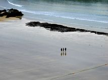 Three girls walk bare foot across Newquay beach, in Cornwall, at the end of the day as the tide departs. stock images