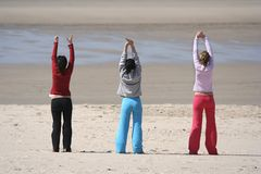 Three girls in the beach. Relaxing (arms up Royalty Free Stock Image