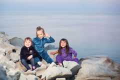 Three girls on the beach. Against the sea on a pile of stones Stock Photos