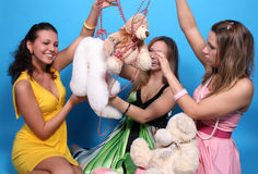Three girls with beads and teddy bears Stock Images
