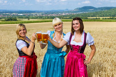 Three girls with beer mugs Royalty Free Stock Photography