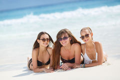 Three girls in bikini sunbathing lying on the sand. Three young girls with a good figure, two girls in black in white bikini, sunglasses,hand, bracelet, lie on stock image