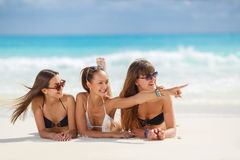 Three girls in bikini sunbathing lying on the sand. Three young girls with a good figure, two girls in black in white bikini, sunglasses,hand, bracelet, lie on royalty free stock photo