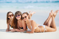 Three girls in bikini sunbathing lying on the sand. Three young girls with a good figure, two girls in black in white bikini, sunglasses,hand, bracelet, lie on stock photography