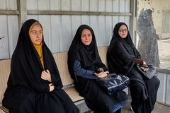 Three girls in black Islamic clothes are waiting for bus. Kashan, Iran - April 27, 2017: Three young Muslim women dressed in dark religious kerchiefs, sit Royalty Free Stock Images