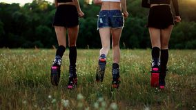 Three girls in boots with springs running through the summer Park at sunset doing sports.  stock video footage