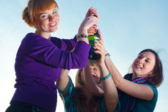 Three girls with a bottle Stock Photography