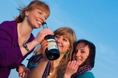 Three girls with a bottle Royalty Free Stock Photos