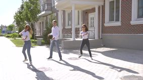 Three girls and boy dressed in similar jeans and shirts dancing in the street stock video