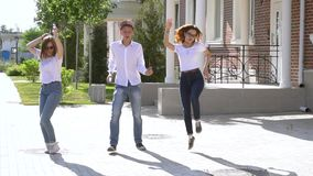 Three girls and boy dressed in similar jeans and shirts dancing in the street stock footage