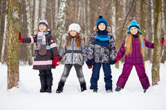 Three girls and boy stand holding hands in winter park Royalty Free Stock Photo
