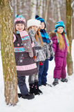 Three girls and boy stand in winter park Royalty Free Stock Image
