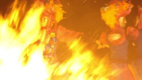 Three girls in bright, colorful ethnic costumes and masks whirling and dancing in front of the burning in the night fire.  stock video footage