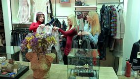 Three girls buy new clothes in a fashion store in a large shopping center. Portrait of three cheerful girls in a clothing store, they choose and try on coats stock video