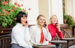 Three girls in cafe speaking on phone. conference call. business meeting at lunch. people connection. modern society. Diversity People Connection Digital stock photo