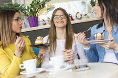 Three girls in a cake shop. Talking about a diet in the cake shop is pointless stock images