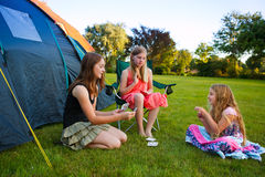 Three girls camping. Three girls playing card beside their camping tent stock photography