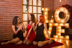Three girls celebrating their birthday. Hen party in identical dress, black and red. Royalty Free Stock Image