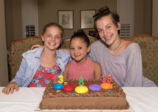 Three girls celebrating their birthdays. A Thirteen year-old girl, and eight year-old girl, and a fifteen year-old teenage girl celebrating their birthday.  They Stock Photos
