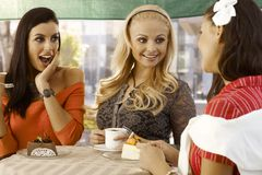 Three girls chatting at outdoor cafe Stock Photos
