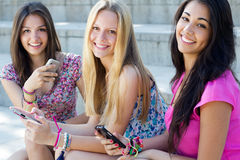 Three girls chatting with their smartphones. At the park stock images