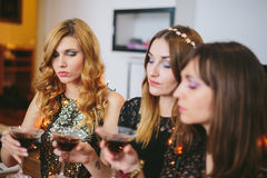 Three girls checking their drinks at a party Stock Photos