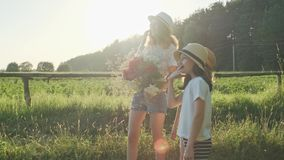 Three girls children with bouquet of flowers show finger on the road, emotions joy and happiness, wait and meet stock video