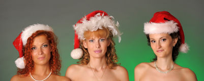Three girls in Christmas hats Stock Images