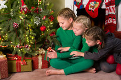 Three girls and a christmas tree Stock Image