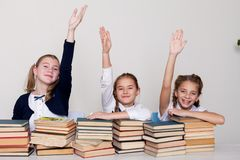 Three girls in the classroom, raised a hand up to answer royalty free stock images