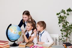 Three girls in the classroom studying geography globe of planet Earth royalty free stock photos