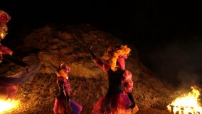 Three girls in colorful ethnic costumes dancing folk dances at the backdrop of the hillside and near the bright fires on. The sides stock video footage