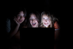 Three girls on the computer at night. Three young girls sitting in the dark all looking at computer screen with a surprised shocked expression stock photos
