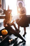Three girls in costumes for party for Halloween posing with glasses of champagne royalty free stock images
