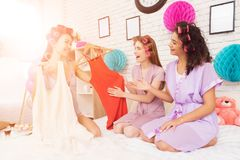 Three girls with curlers in their hair coosing between two dresses. They are celebrating women`s day March 8. stock photos