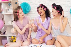 Three girls with curlers in their hair drinking champagne. They are celebrating women`s day March 8. Stock Photography