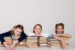 Three girls schoolgirls at a desk with books on the lesson at school royalty free stock photo