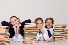 Three girls schoolgirls at a desk with books on the lesson at school stock photography