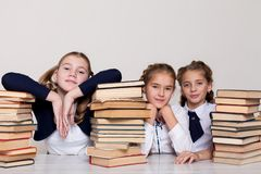 Three girls schoolgirls at a desk with books on the lesson at school royalty free stock photos