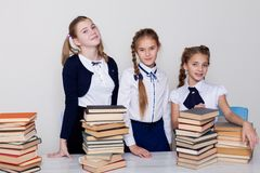 Three girls schoolgirls at a desk with books on the lesson at school royalty free stock image