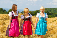 Three girls in dirndl. Standing in a field stock photography