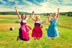 Three girls in dirndl. Jumping on meadow Royalty Free Stock Images
