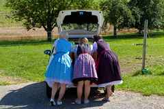 Three girls in Dirndl looking in a car-boot Royalty Free Stock Photos