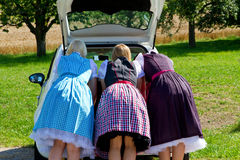 Three girls in Dirndl looking in a car-boot Stock Photos