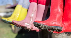Three girls in dirty gumboots. Close up of muddy gumboots in different colors. Three girls sitting with crossed legs and showing dirty shoes Royalty Free Stock Photography