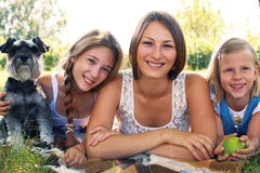 Three girls and a dog Stock Images
