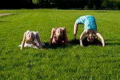 Three girls doing exercises, in nature Royalty Free Stock Photography
