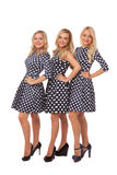Three girls in dot dresses and black shoes Royalty Free Stock Images